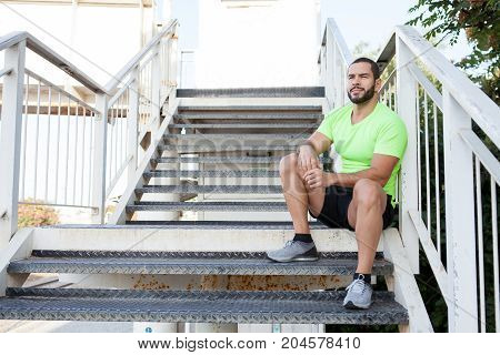 Dreamy handsome man resting on staircase and contemplating landscape around. Calm young runner building up strength before training outdoors. Sportsman concept