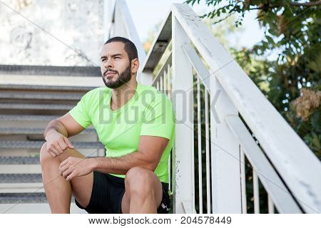 Pensive brutal man contemplating nature around while resting after training. Purposeful handsome young athlete thinking of future. Dreams concept