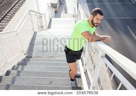 Pensive muscled man standing on staircase and looking at highway. Contemplative young athlete relaxing after training outdoors. Urban sport concept