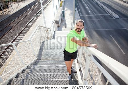 Serious sporty man leading healthy lifestyle and running on staircase. Tired handsome runner leaning on railing and looking at camera. Fitness concept