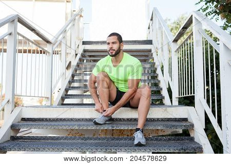 Sporty handsome guy tying shoe and sitting on step while training outdoors. Dreamy young man running in morning. Sport as lifestyle concept