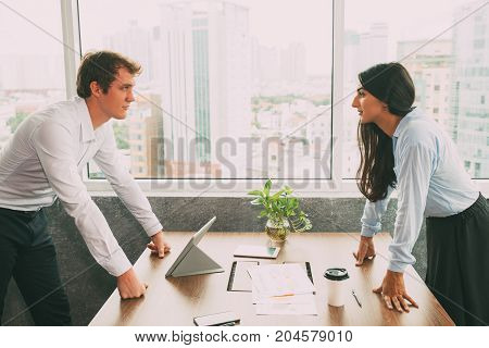 Confident business rivals being in conflict looking at each other with hostile expressions. Serious business people leaning on table and arguing about strategy. Opposition or business competition concept