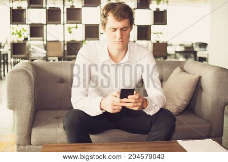 Displeased young businessman reading message on phone. Concentrated manager using gadget while sitting on sofa in waiting room. Problems concept
