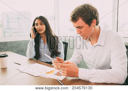 Multiethnic business people solving work issues. Pensive Indian female manager talking on phone, while concentrated man searching of information on Internet using tablet. Entrepreneurship concept