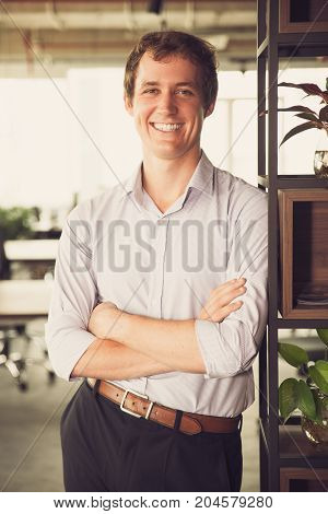 Satisfied male manager pleased with success working in large company. Cheerful handsome businessman leaning on shelves and looking at camera in office. Leadership concept