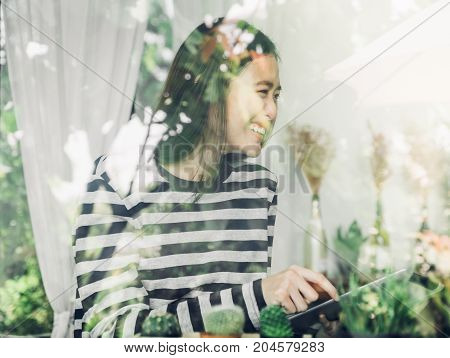 Asian Woman Sitting At Cafe And Laughing With Friend And Use Tablet Computer In Restaurant ,window S