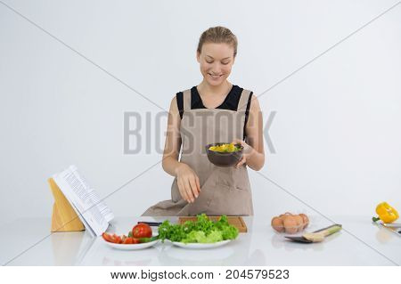Happy housewife cooking tasty and healthy food. Cheerful beautiful young woman making favorite recipe and holding bowl with salad. Domestic kitchen concept