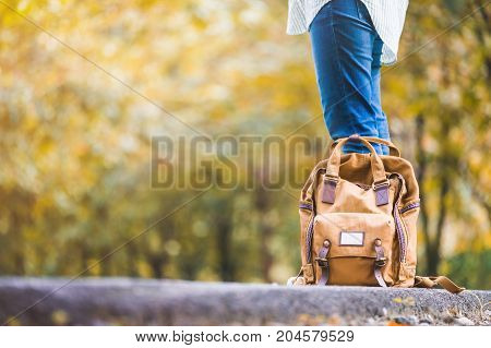Close Up Backpack Of Woman Backpacker Standing On Countryside Road With Tree In Autumn Fall Seasonal