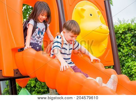 Two kids friends having fun to play together on children's slide at school playgroundback to school activity