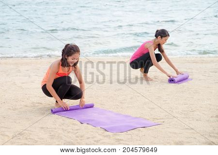 yoga student keep yoga mat after finish outdoor beach classHealthy balance lifestyle sport concept.