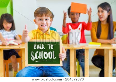 Kid boy thumbs up and holding blackboard with back to school word with diversity friends and teacher at backgroundKindergarten school.education concept