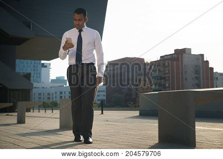 Serious businessman in white shirt and tie, holding newspaper, walking outsides and using smartphone. Office worker checking mailbox or reading message on phone. Modern technology concept