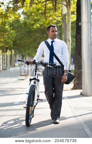 Hispanic businessman walking with shoulder bag and bike in park. Young male office employee having stroll after work. Lifestyle concept
