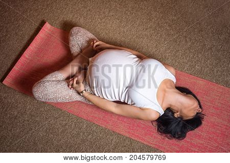 Pregnancy Yoga and Fitness concept. Healthy maternity lifestyle concept. 40 week pregnant middle aged caucasian woman doing yoga exercises laying on the back with her legs in lotus pose. Top view