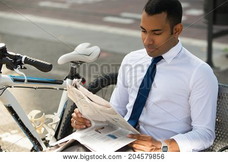 Concentrated Hispanic businessman sitting on bench in park, reading newspaper, bike nearby. Young male office worker reading recent news during lunchtime. Business news concept