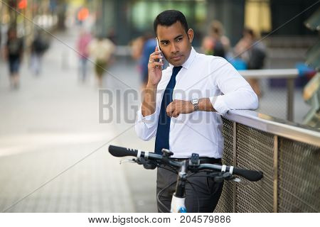 Concentrated Hispanic businessman with bike standing and talking on phone with colleague. Young office worker using smartphone in city. Modern technology concept