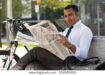 Handsome Hispanic businessman sitting on bench, holding paper, looking at camera, bike nearby. Young male office worker reading newspaper in park