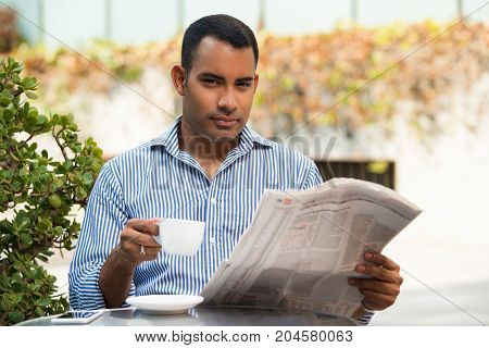 Handsome Hispanic young man with cup of coffee and newspaper sitting in outdoor cafe. Executive manager reading recent news and drinking coffee during lunchtime. Lunch concept
