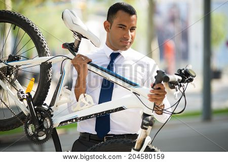 Handsome Hispanic businessman wearing white shirt and tie, carrying his broken bike, looking at camera. Accident concept