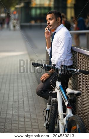 Handsome Hispanic office worker stopping his bike and talking on phone. Young businessman using smartphone in city. Modern technology concept