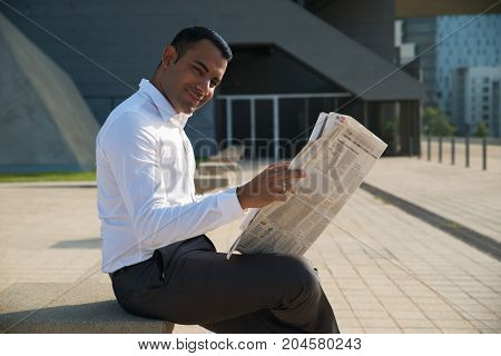 Handsome Latin businessman sitting outside office, holding newspaper and smiling at camera. Happy young male office worker reading recent news. Business news concept