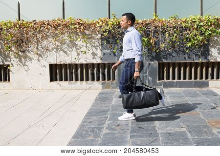 Hispanic young man wearing striped shirt and navy pants, carrying leather bag and running. Businessman hurrying up in gym. Lifestyle concept