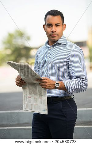 Portrait of confident Hispanic young man standing outdoors, holding newspaper, looking at camera. Business news concept
