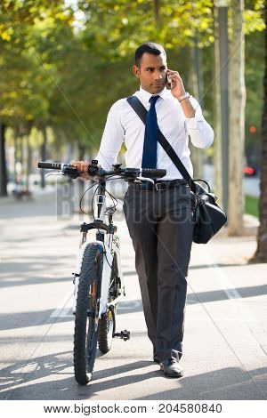 Serious Hispanic businessman with bike walking in park and talking on mobile phone. Young office worker using smartphone. Modern technology concept