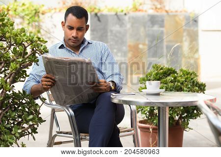 Serious Hispanic young man sitting in outdoor cafe, reading newspaper and drinking coffee. Confident executive manager reading recent news during lunchtime. Business news concept