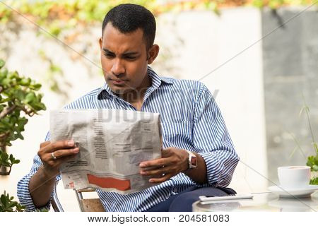 Serious Hispanic young man sitting in outdoor cafe, reading newspaper and drinking coffee. Frowning executive manager reading recent news during lunchtime. Business news concept