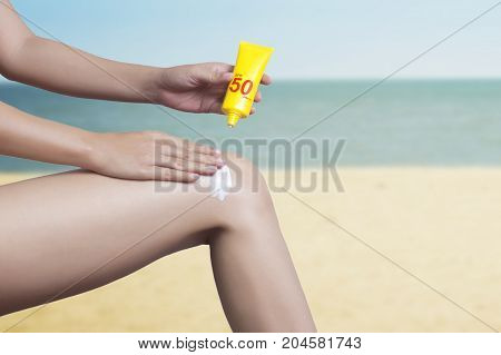 woman applying sunscreen on her leg with sea background. SPF sunblock protection concept. Travel vacation clipping path include