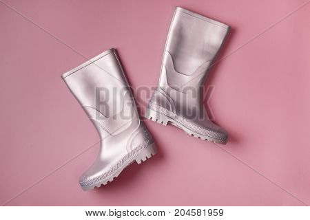 Autumn bright composition: Stylish silver gumboots. Pink background Top view. Flat lay.