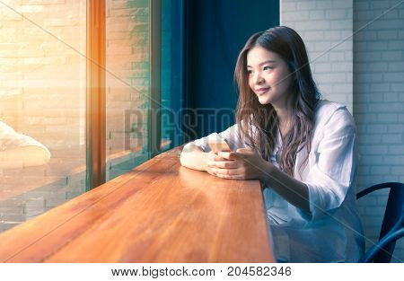 young happy asian woman looking out the window and holding her phone at a cafe with warm light coming in from the window duo tone colors warm high light and cool blue shadow good for communication or relationship concept