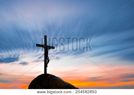 Jesus Christ on the cross over sky bright background
