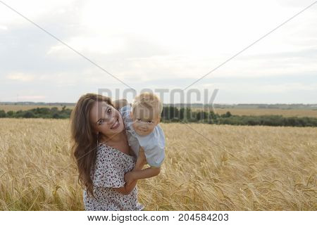 Happy mother with her little son walking through a wheat field. Mother father and child leisures together outdoor. Mom dad and kid on summer field