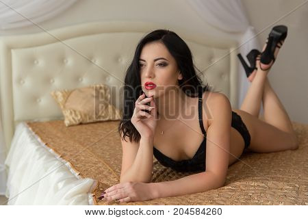 Young and sexy brunette laying on the bed.