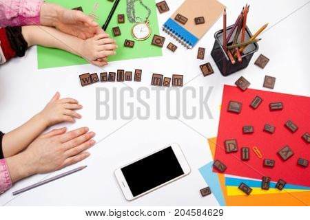 Working mom concept. hands of mother and child on working desk, free space for text.