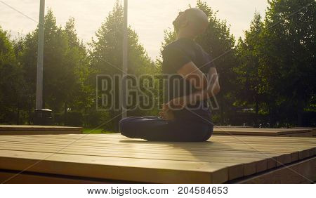 A man doing yoga exercises in the park in summer. Baddha padmasana