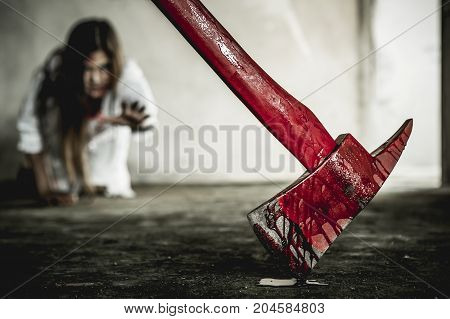 Zombie woman reaching out to grab the ax. Women dress imitating zombies on Halloween.