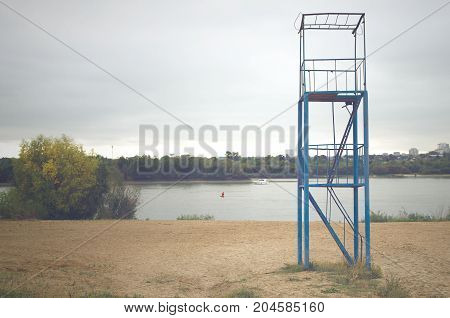 Rescue tower on the autumn river beach.