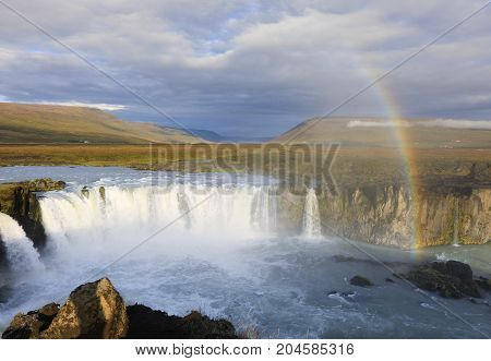 The rainbow over the famous Icelandic waterfall Godafoss Falls. Top tourist destination in Iceland - largest Iceland's waterfall Godafoss