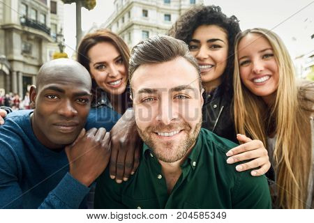 Multiracial group of friends taking selfie in a urban street with a caucasian man in foreground. Three young women and two men wearing casual clothes.
