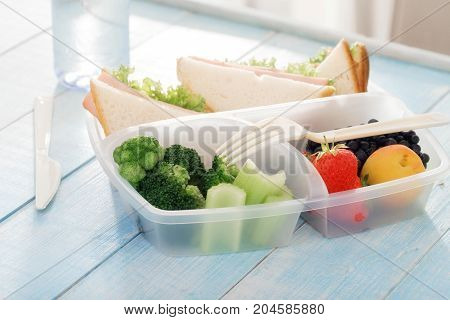 Full lunch box of healthy food. Sandwich strawberry peach blueberries broccoli and celery in a lunch box on wooden table close up. Healthy lunch concept