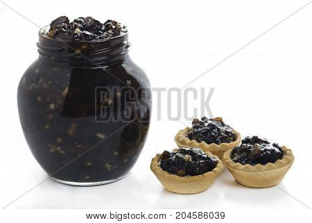 full jar of traditional Christmas mincemeat homemade with mixed fruits with three mince tarts to the side on a white isolated background