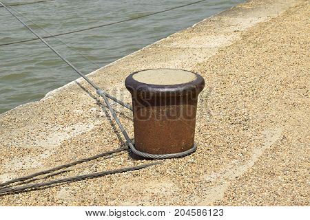 Bollard on the river bank next to the water