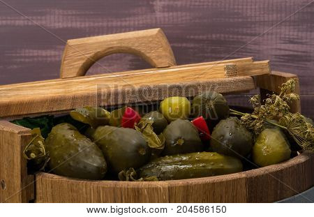 cucumbers with red pepper lie in a barrel under the lid