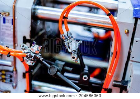 Fragment of the injection molding machine. Abstract industrial background.