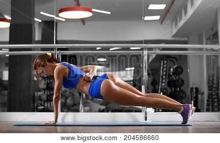Attractive young woman is doing push ups exercise while working out in gym. Beautiful slender brunette girl in blue sportswear.