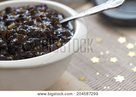 macro image of homemade traditional Christmas mincemeat made with mixed fruit and brandy in a white bowl focus on the subject background de focused to ad copy space