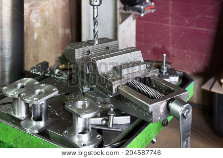 Drilling machine. The drill bit is installed in the drill chuck. Machine vice, metalworking shop.